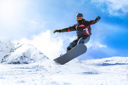 Homme sautant avec planche à neige depuis la colline de montagne Banque d'images