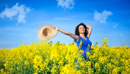 outstretched arms: Attractive woman with outstretched arms in rapeseed field in summer