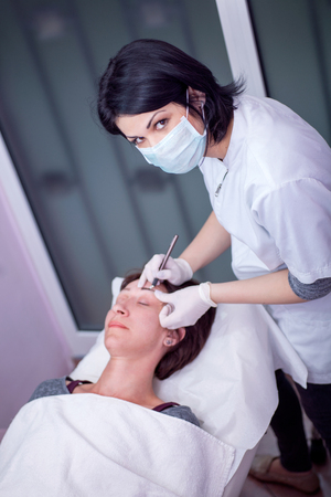 Cosmetologist applying permanent make up on eyebrows Banque d'images