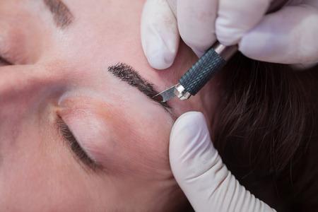 mujer maquillandose: Cosmetologist aplicar maquillaje permanente en las cejas