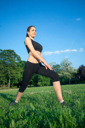 ifestyle: Young woman stretching in park