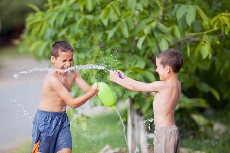 deux garçons jouer et aspergés d'eau dans un parc ou cour de la maison des enfants heureux à l'extérieur sur une journée d'été, pulvérisé avec des ballons remplis d'eau