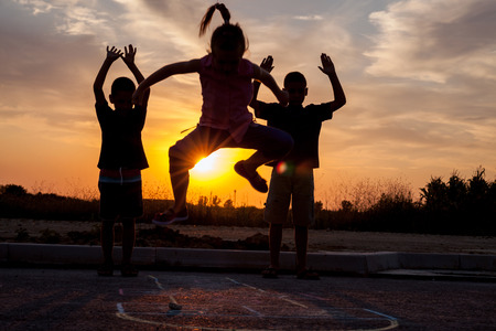hopscotch: young boy and a girl playing hopscotch in the sunset Stock Photo