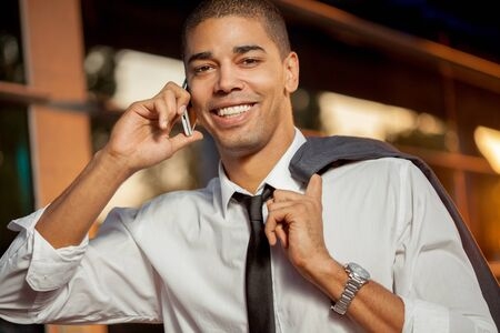 black professional: handsome happy  young businessman talking on mobile phone ,outdoors