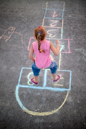 hopscotch: Cute blonde girl playing hopscotch on the street