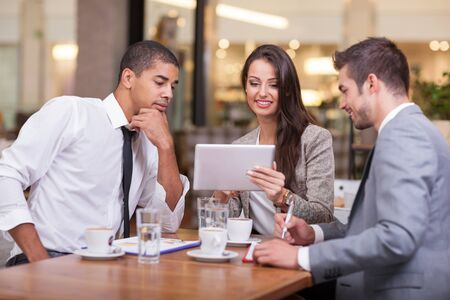 casual business man: Young businesspeople having a business meeting at coffee table Stock Photo