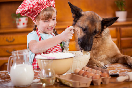 a little girl and her friend dog make a mess in the kitchen Standard-Bild
