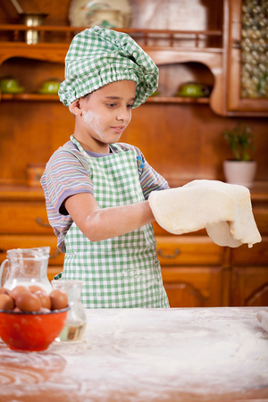 beautiful little boys: happy smiling young boy chef in kitchen Stock Photo