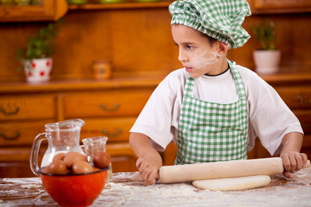 beautiful little boys: young boy chef in kitchen making dough Stock Photo