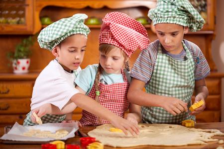 three children: three children preparing cookies in the kitchen Stock Photo