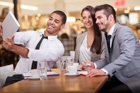 profesionistas: Tres hombres de negocios exitosos que toman una feliz selfie en el restaurante