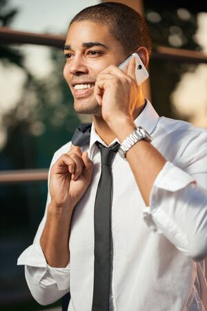 lazo negro: handsome happy  young businessman talking on mobile phone ,outdoors
