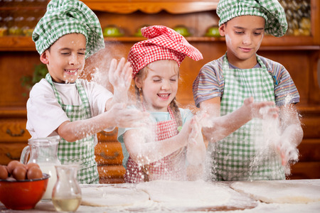 home cooking: children playing with flour in the kitchen