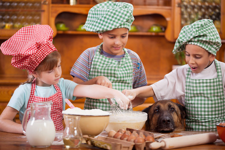 Three little chefs enjoying in the kitchen making big mess. German Shepherd watching