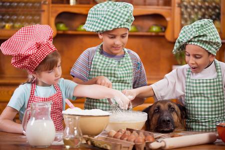 Three little chefs enjoying in the kitchen making big mess. German Shepherd watching