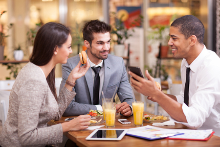businessman smiling: Three Business people Having Meeting In Outdoor Restaurant