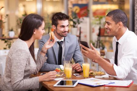 gente reunida: Tres hombres de negocios que tienen reunión en restaurante al aire libre Foto de archivo