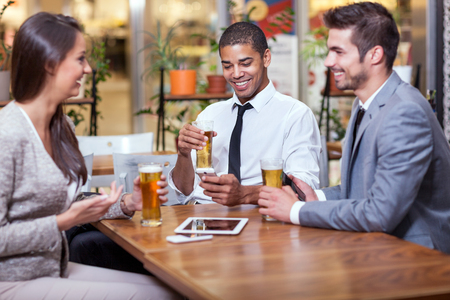 business suit: group of young businessman in restaurant drinking beer