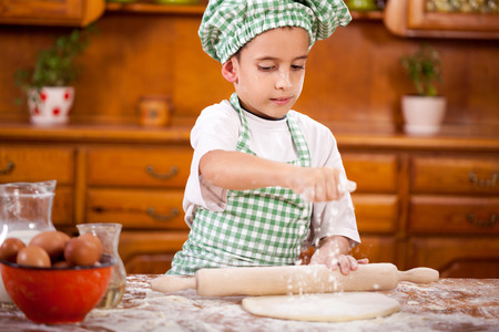 young female: happy smiling young boy chef in kitchen making dough Stock Photo