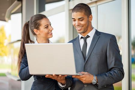 hombres trabajando: j�venes serios hombres de negocios exitosos con el ordenador hablando de trabajo,