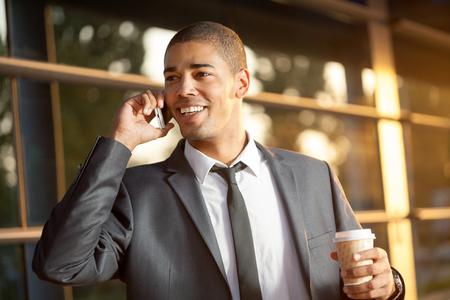bel homme: beau jeune homme d'affaires heureux de parler sur t�l�phone mobile, � l'ext�rieur Banque d'images