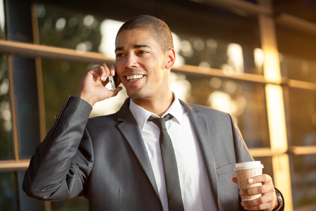 handsome: handsome happy  young businessman talking on mobile phone ,outdoors