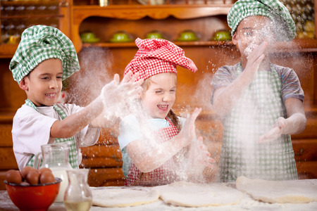 children playing with flour in the kitchen