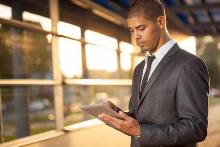 Successful business man with digital tablet outside