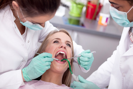 Dentist examines the oral cavity of the patient on the dentists chair
