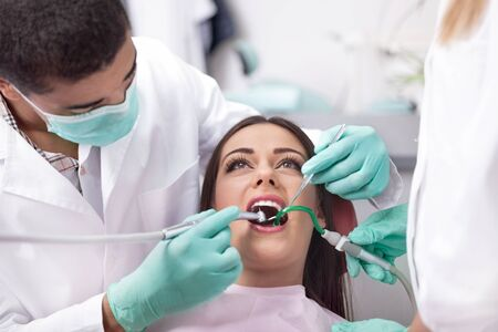 treating: dentist is treating teeth of the female patient Stock Photo