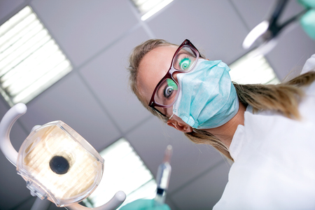 work wear: scary and funny dentist working with a patient in protective work wear