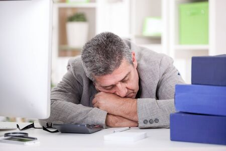 sleeping at desk: exhausted senior businessman sleeping in office