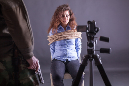 mujer con arma: atado mujeres golpeadas, en manos de secuestradores delante de la cámara