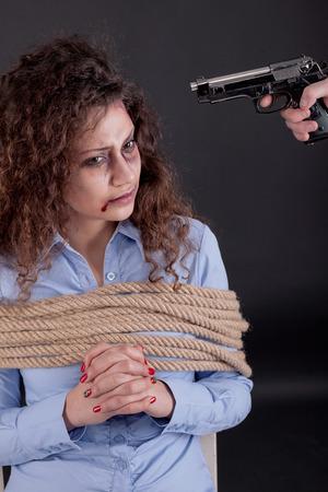 holding gun to head: terrorists holding a gun to a womans head Stock Photo