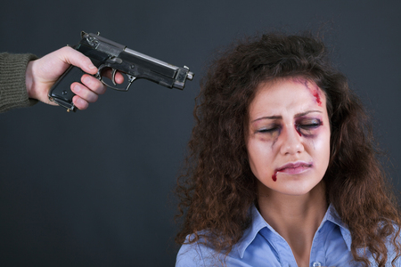 hostages: terrorists holding a gun to a womans head Stock Photo