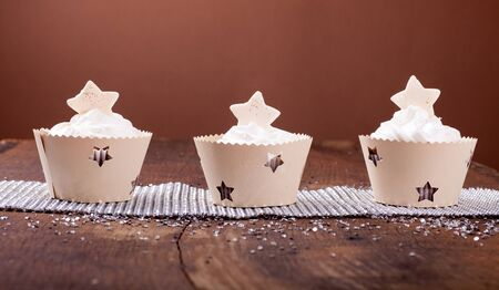 cake pick: Holiday decorated cupcakes on wooden background Stock Photo