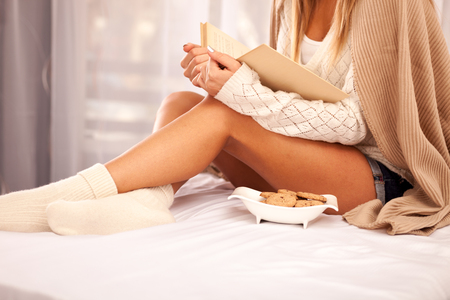 legwarmers: woman on the bed with book