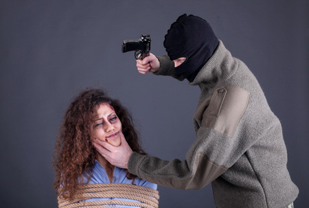 terrorists: terrorists holding a gun and threatens woman