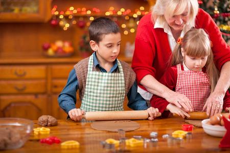 grandmother grandchild: grandchildren and  grandmother baking Christmas cookies