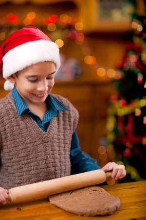 boy with rolling pin baking in kitchen Christmas cakes Banque d'images
