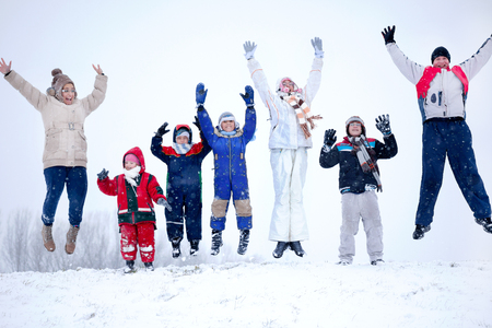 Joyful family jumping in the air in the snow