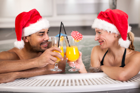 water hottub: Beautiful woman and man with santa hat relaxing in jacuzzi at spa center