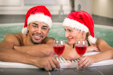 water hottub: Happy christmas santa couple in hot tub. Vacation