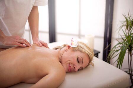 professional masseur doing massage of female back in the beauty salon