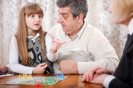 to be or not to be: grandfather, grandmother with her granddaughter in the house playing board games (Man do not be angry)