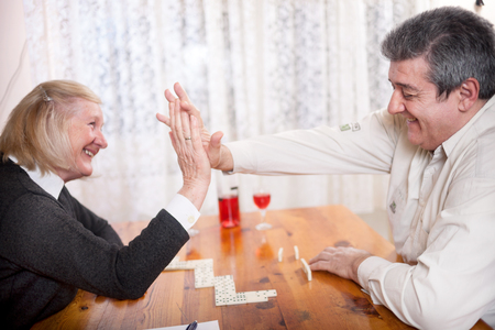 eldercare: Couple playing dominoes in living room smiling