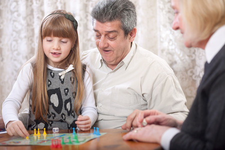 to be or not be: grandfather, grandmother with her granddaughter in the house playing board games (Man do not be angry)