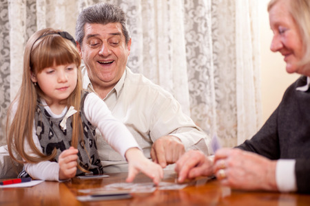 grandfather with grandmother and granddaughter playing cards Stock Photo