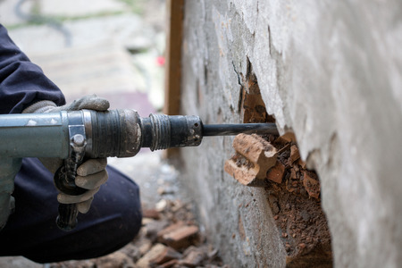 worker with pneumatic hammer drill perforator equipment making hole in wall at construction site