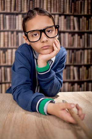 funny glasses: funny boy with eye glasses in library Stock Photo